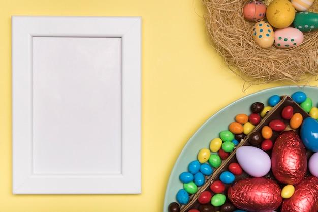 イースターフードと白いフレームでフラットレイアウト装飾 無料写真