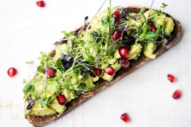 Ломтик хлеба с пастой из авокадо и овощами высокий вид Бесплатные Фотографии
