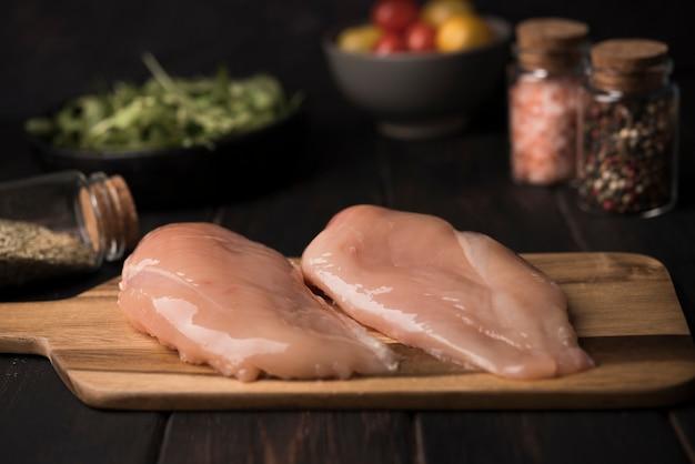Куриная грудка крупным планом на деревянной доске с ингредиентами Бесплатные Фотографии
