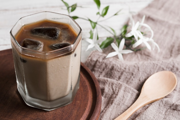 Кофе с кубиками льда в стакане и цветы Бесплатные Фотографии