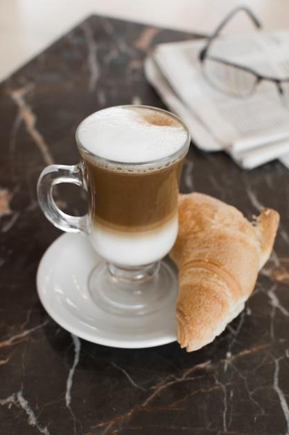 Кофе латте с круассаном и размытыми бокалами Бесплатные Фотографии