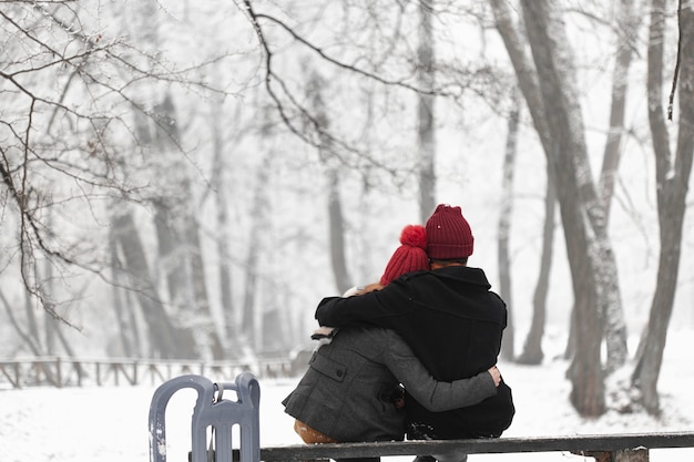 素敵なカップルのベンチに座ってハグ 無料写真