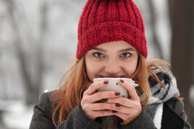 彼女の顔の近くのお茶のカップを保持している女性 無料写真