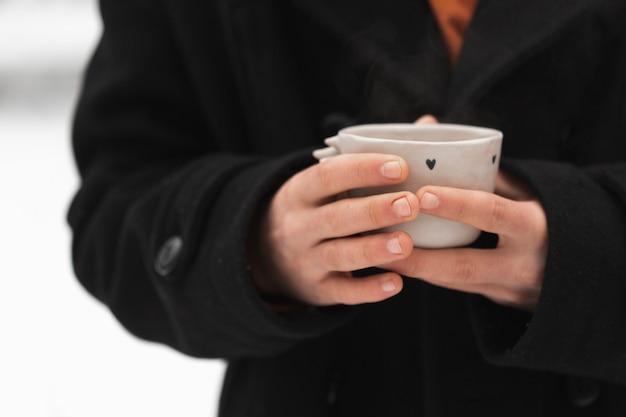 Руки человека, держащего чашку горячего чая Бесплатные Фотографии
