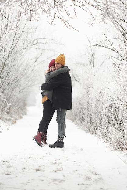 Пара, обнимающая друг друга зимой на открытом воздухе Бесплатные Фотографии