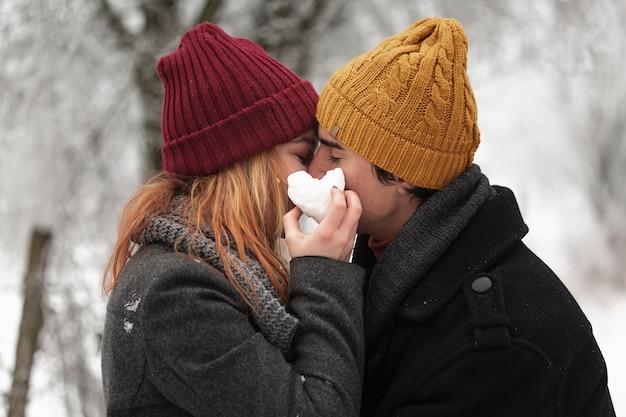 若いカップルが冬のシーズンミディアムショットでキス 無料写真