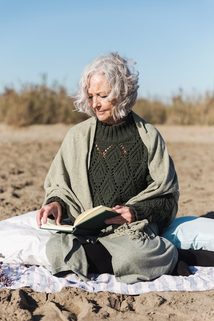 Старший леди, чтение книги вид спереди Бесплатные Фотографии