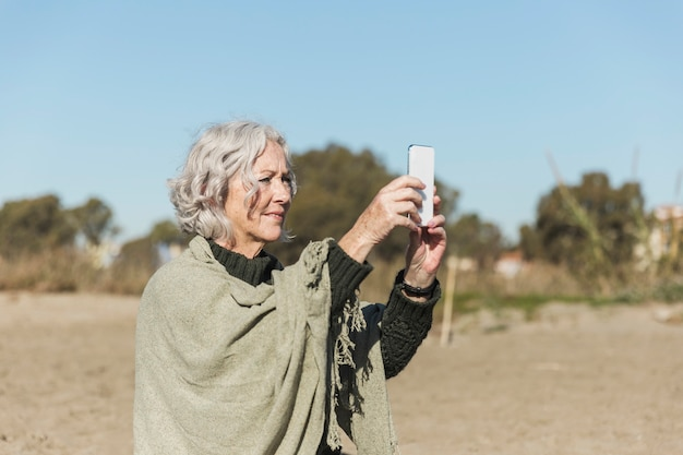 Средний снимок женщина делает фотографии на открытом воздухе Бесплатные Фотографии
