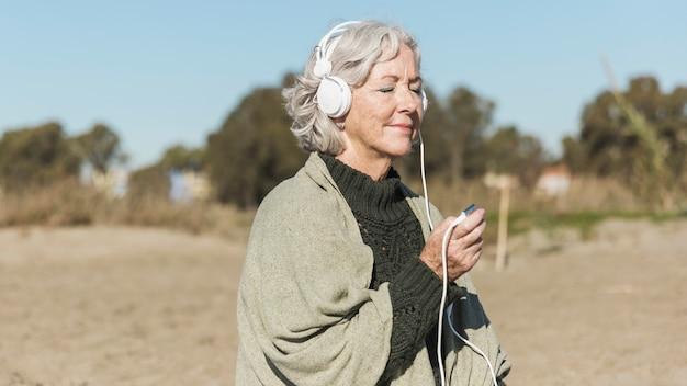 Средний выстрел старой женщины, слушающей музыку Бесплатные Фотографии