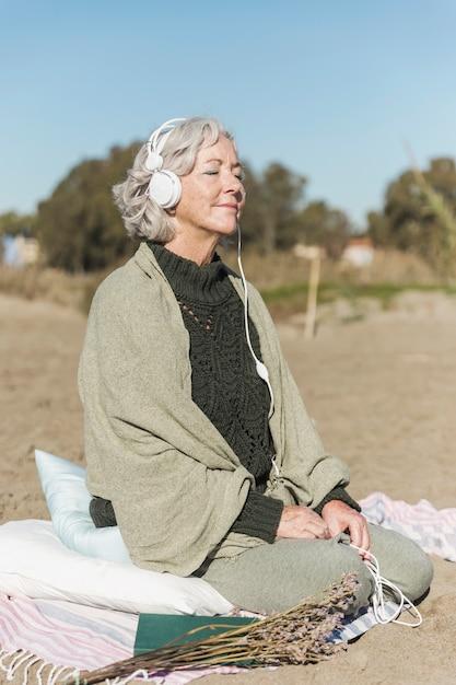 Полный выстрел женщина медитирует на открытом воздухе Бесплатные Фотографии