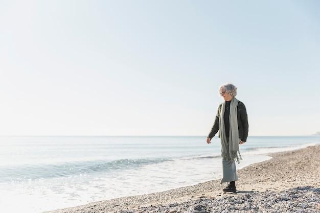 Полный выстрел старуха, идущая на побережье Бесплатные Фотографии