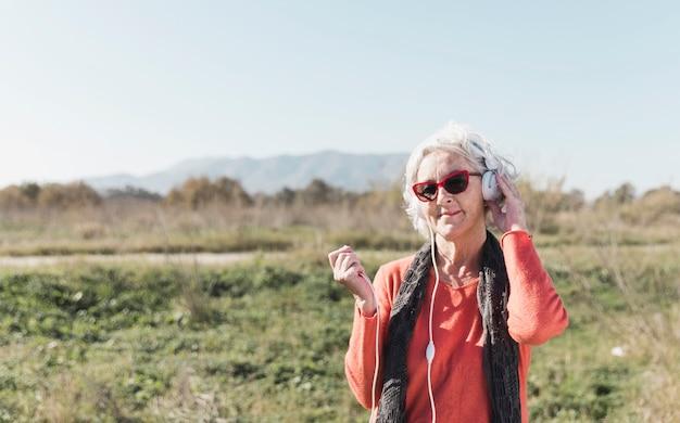 Средний выстрел женщина с наушниками на открытом воздухе Бесплатные Фотографии