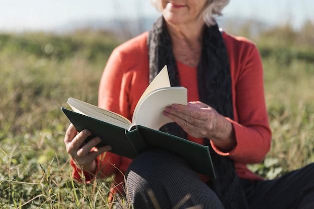Крупным планом женщина с книгой на открытом воздухе Бесплатные Фотографии