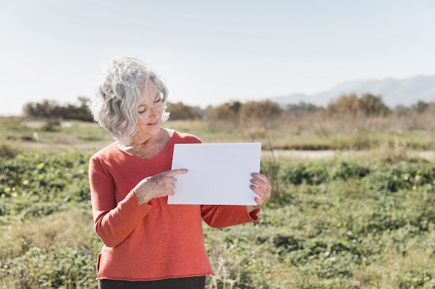 Женщина с куском бумаги на открытом воздухе Бесплатные Фотографии