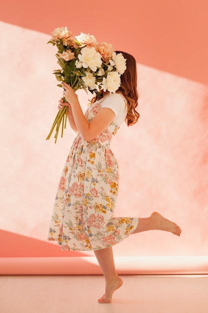 花の花束の完全なショットを保持している女性 無料写真
