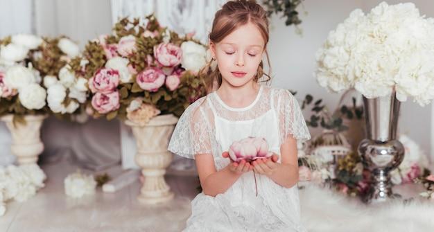 花ミディアムショットを保持している罪のない女の子 無料写真