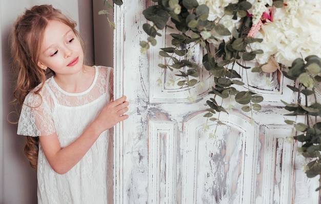 ドアの横にポーズの罪のない女の子 無料写真