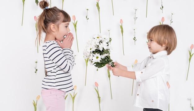 女の子に花をあげる少年 無料写真
