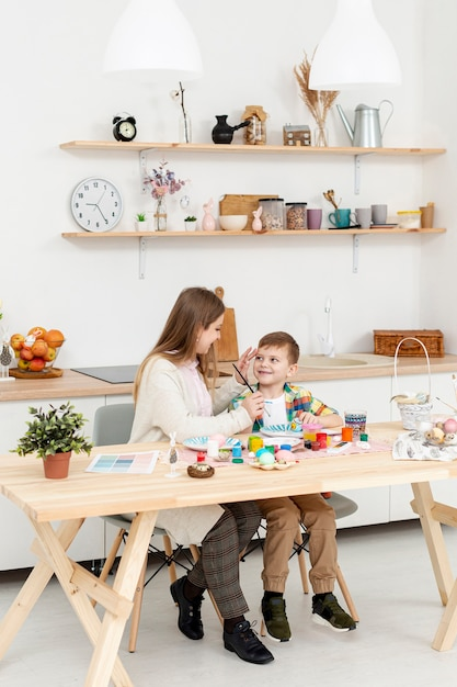 Высокий угол мама и сын крася яйца на пасху Бесплатные Фотографии