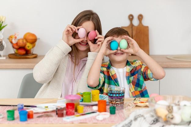 Вид спереди мама и сын с крашеными яйцами Бесплатные Фотографии