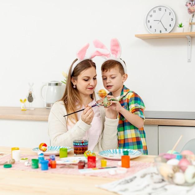 卵を塗るウサギの耳を持つ高角度ママと息子 無料写真
