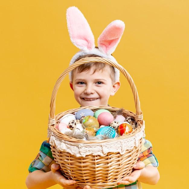 Маленький мальчик держит корзину с крашеными яйцами Бесплатные Фотографии