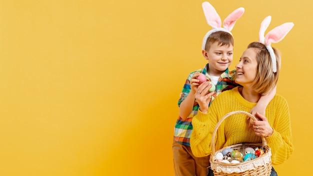 Копия пространство мама и сын с корзиной, полной крашеные яйца Бесплатные Фотографии