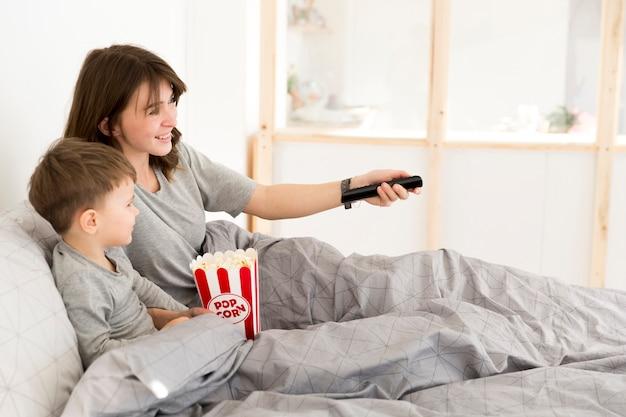 母と息子はベッドでテレビを見て 無料写真