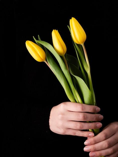 黄色のチューリップと正面の手 無料写真