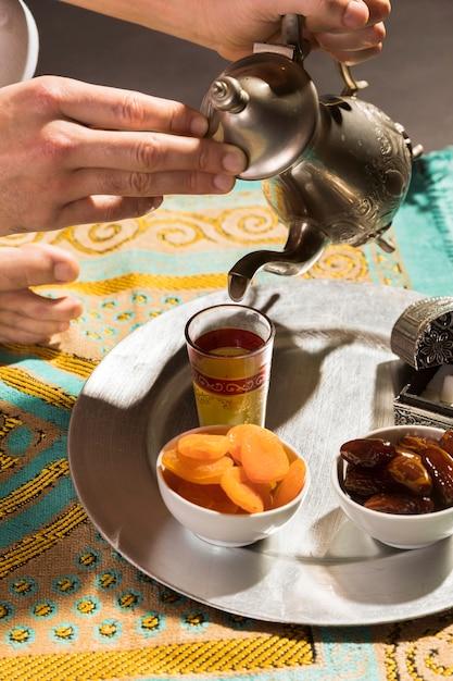 小さなカップ高いビューでお茶を注ぐ男 無料写真