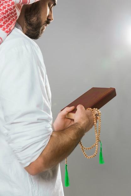コーランを保持し、ビーズを祈るイスラム教徒の男性 無料写真