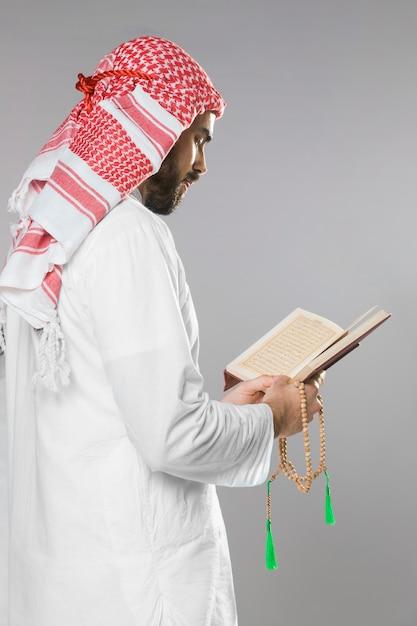 イスラム教徒の男性がコーランを読んで、ビーズを保持 無料写真