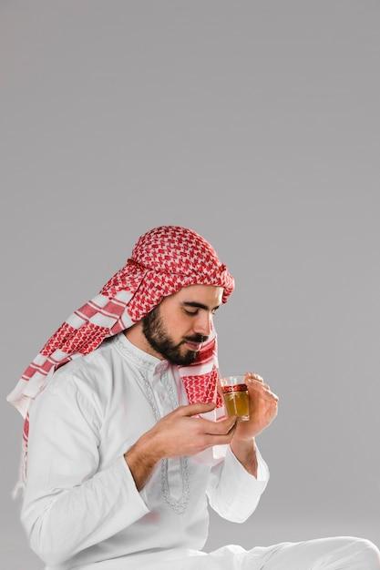 スマイリーのイスラム教徒の男性は、伝統的なお茶の肖像画を楽しんでいます 無料写真
