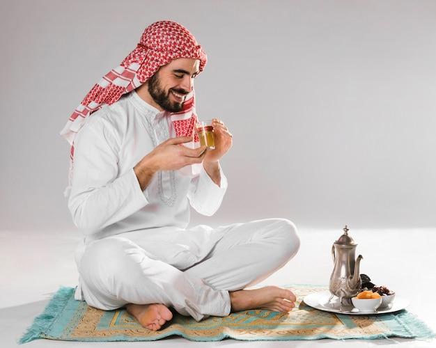 スマイリーのイスラム教徒の男性は伝統的なお茶を楽しんでいます 無料写真