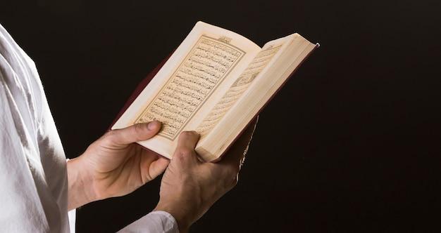 手で開いているコーランを持つ男 無料写真