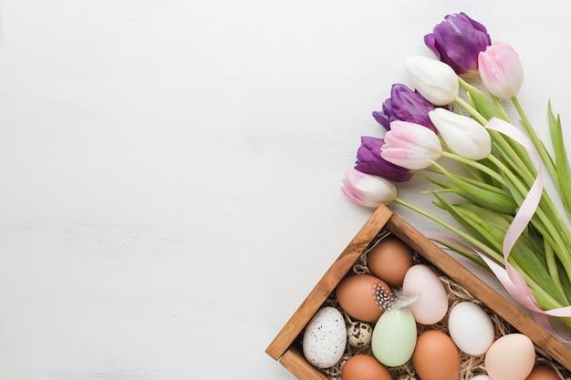 Вид сверху коробки с яйцами для пасхальных и разноцветных тюльпанов Бесплатные Фотографии
