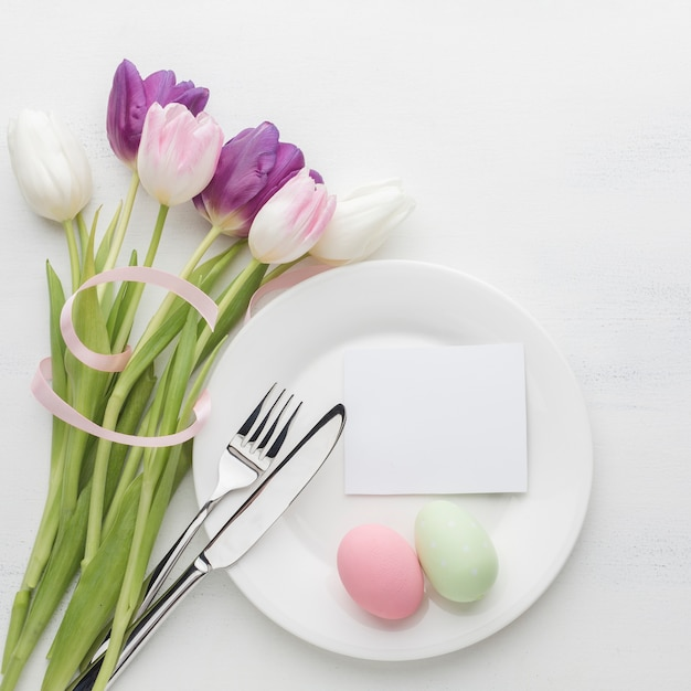 Вид сверху тарелка с пасхальными яйцами и тюльпаны со столовыми приборами Бесплатные Фотографии