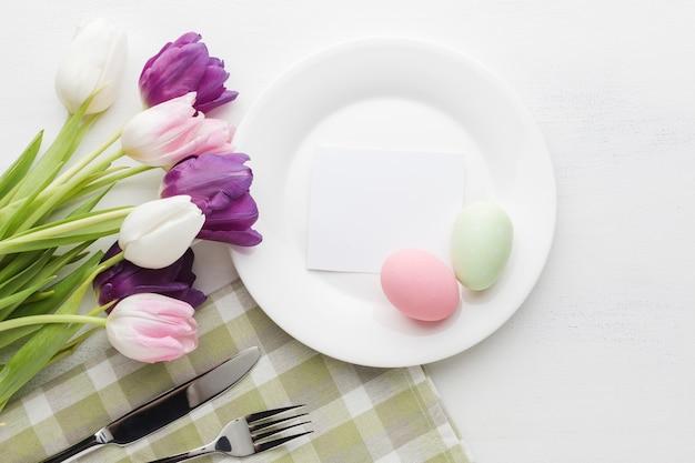 Плоская планировка из разноцветных тюльпанов с тарелкой и пасхальными яйцами Бесплатные Фотографии