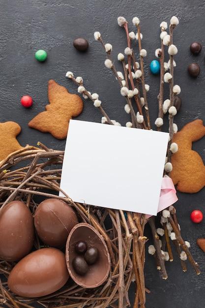 クッキーと紙の上に巣のチョコレートイースターエッグのトップビュー 無料写真