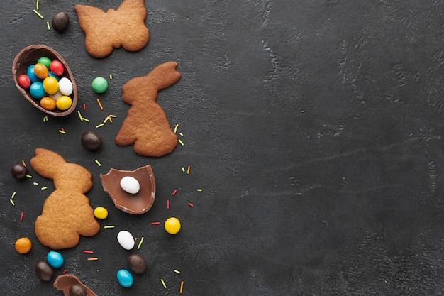 コピースペースとお菓子でいっぱいのチョコレートの卵とイースターのバニーの形をしたクッキーのフラットレイアウト 無料写真
