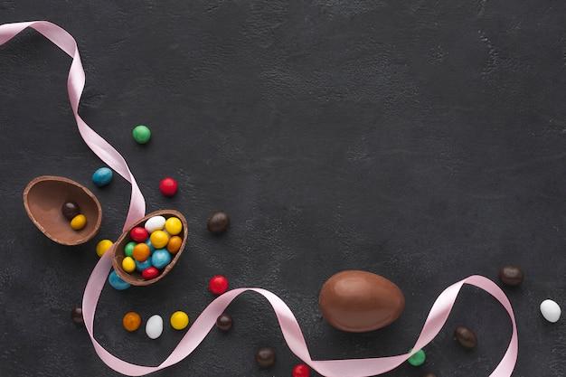 カラフルなキャンディーとコピースペースで満たされたチョコレートのイースターエッグのフラットレイアウト 無料写真