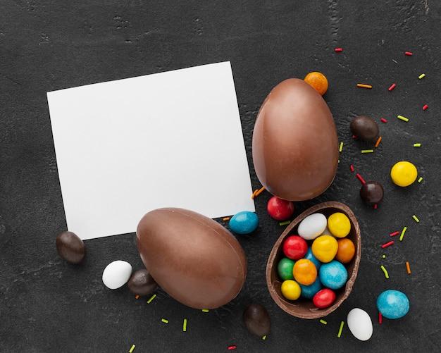 Плоская кладка шоколадных пасхальных яиц с красочными конфетами и куском бумаги Бесплатные Фотографии