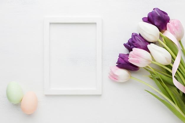 フレームとイースターエッグと美しいチューリップのトップビュー 無料写真