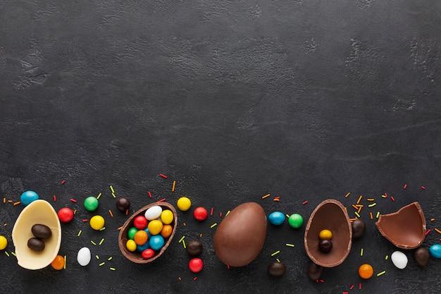 カラフルなキャンディーで満たされたチョコレートイースターエッグのトップビュー 無料写真