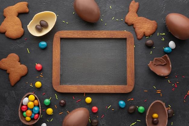 Вид сверху пасхальных шоколадных яиц с печеньем и доске в форме зайчика Бесплатные Фотографии