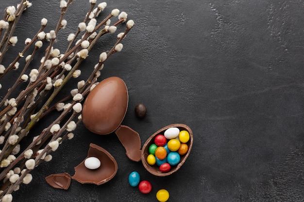 カラフルなキャンディと花とチョコレートのイースターエッグのトップビュー 無料写真
