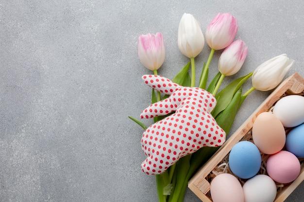 Плоская кладка тюльпанов и красочные пасхальные яйца в коробке Бесплатные Фотографии