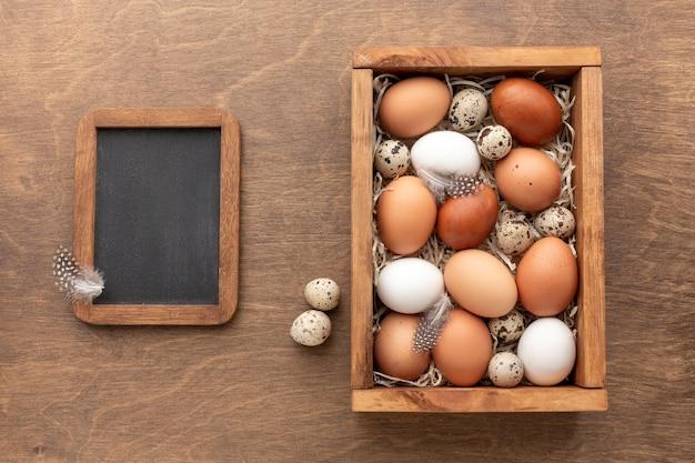 Взгляд сверху классн классного с коробкой полной с яичек на пасха Бесплатные Фотографии