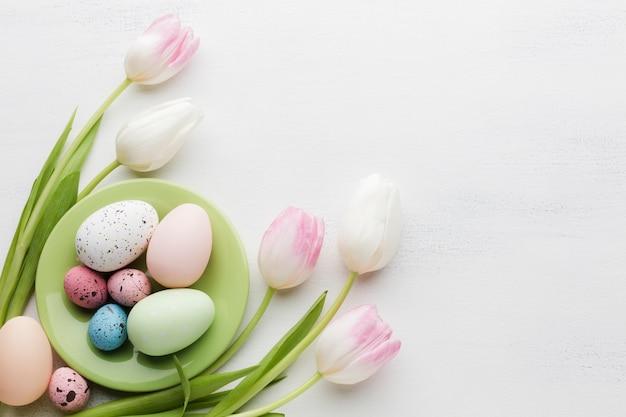 Вид сверху разноцветных пасхальных яиц с тюльпанами Бесплатные Фотографии