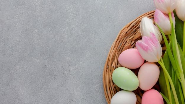 チューリップバスケットでイースターのカラフルな卵のトップビュー 無料写真